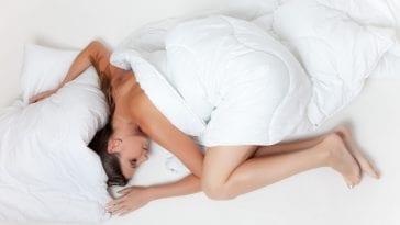 Kobieta, leżąca w łóżku.
