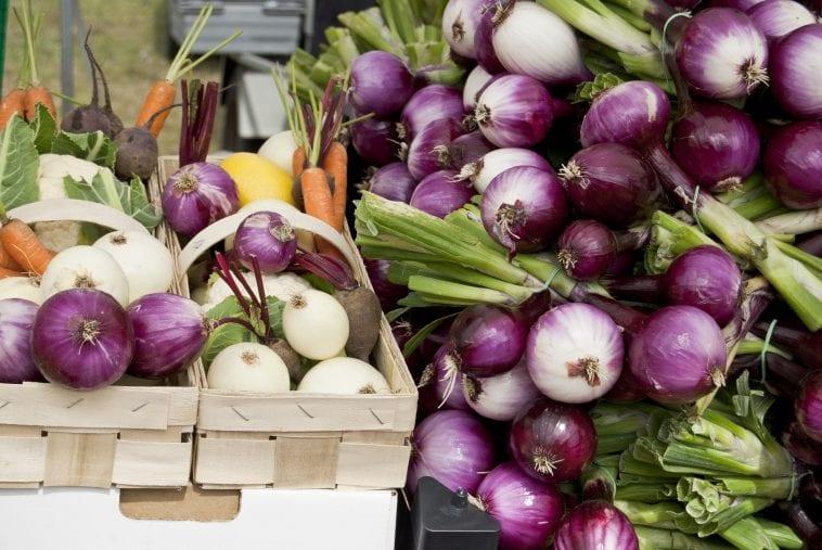 Duża ilość cebuli w koszu z warzywami.