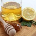 Cytryna, woda i miód na drewnianej desce.